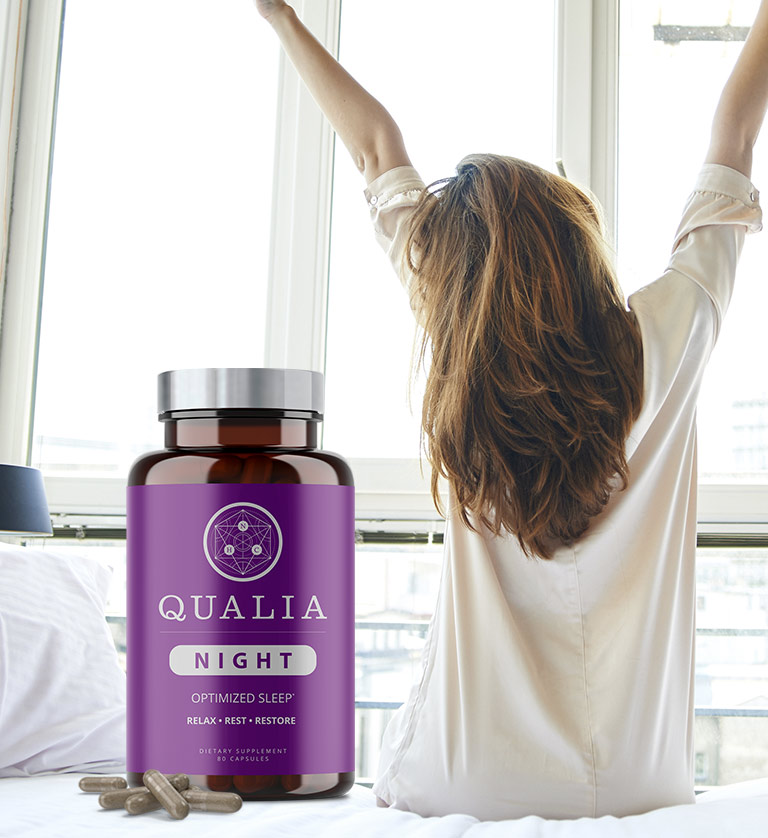Qualia Night Bottle with Woman Stretching while sitting on bed